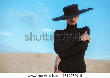 Mysterious beautiful woman with red lips wearing big hat hiding her face, posing gracefully on sand at the beach, copy space. Secret, mystery concept