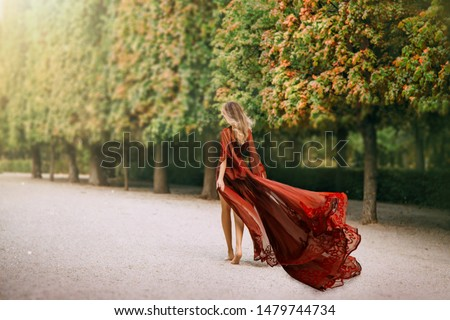Mysterious blond woman in a red evening dress, walks in the autumn park barefoot. The wind blows a long train and hair. Queen in her garden. Rear view