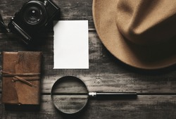 Mysterious detective game concept notebook leather cover sheet white paper felt brown hat portable mirrorless microthird digital photo camera big vintage magnifier isolated on black aged wood table