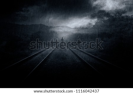 Stock Photo mysterious fantasy scene with ghostly shadow on railroad tracks