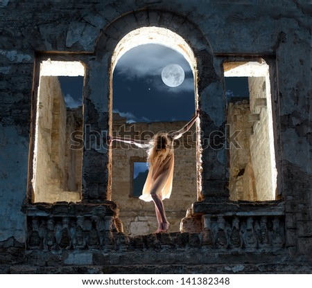 Mysterious female figure standing in the arc of the ruined building in full moon night