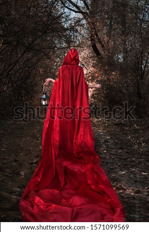 Mysterious figure in the dark forest with little red riding hood. With lantern in the hand