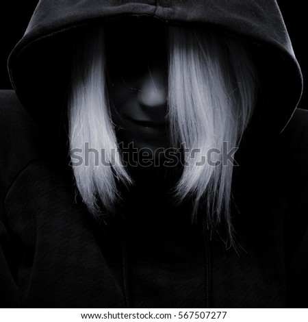 Stock Photo Mysterious girl with hood isolated on black background.