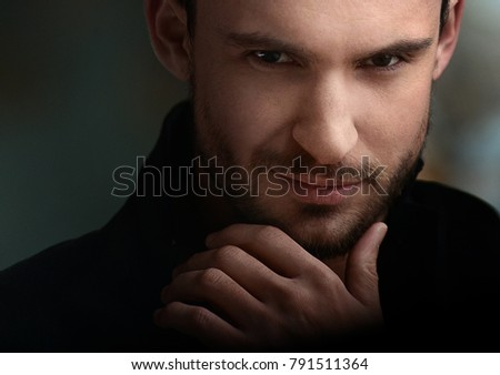 Mysterious handsome man with sneaky look. man with beard smiling. sexy guy in a dark jacket with confident face. Sexy and smart man with beautiful eyes. businessman on a dark romantic background.
