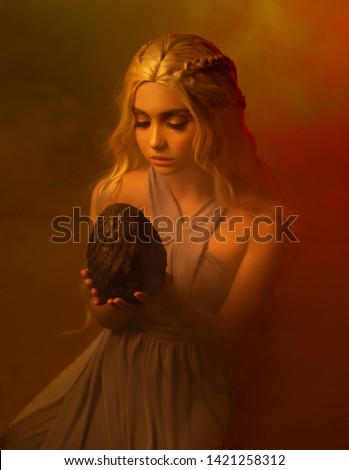 mysterious lady with blond braided hair is sitting in a dark room in an old vintage dress, girl is holding a terrifying big prickly egg, unexpected find, mythical creature in the hands of human.