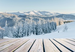 Mysterious landscape majestic mountains in winter and shabby table . Magical snow covered tree. Photo greeting card. Bokeh light effect, soft filter. Carpathian Ukraine. Happy New Year.