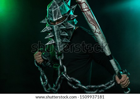 Mysterious man in a helmet with a bat and chains in black wear. Fantasy book or computer game cover concept on halloween disco party.