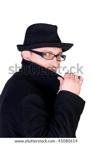 Mysterious man wearing a black hat and a black coat with a raised collar