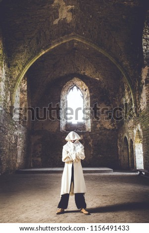 Mysterious man with white hood in medieval costume stand mysteriously in ancient castle ruins. Role play or medieval life concept. #1156491433