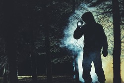 Mysterious Men with Flashlight in His Hand In Dark Foggy Forest. Poacher, Hunter or Rescuer During Rescue Action.