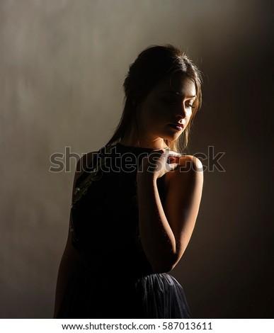 mysterious model posing in the shadows in dark studio #587013611