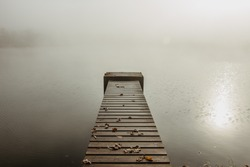 Mysterious morning  by lake. Foggy autumn mystery atmosphere. Wooden pier on the pond.Magic mood. Misty fall day. Speechless place. Relaxing meditation without people.Silence scene.Serenity background