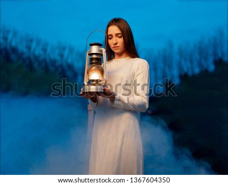 Mysterious mystical girl in a dark night forest with a kerosene lamp in her hands Halloween concept #1367604350