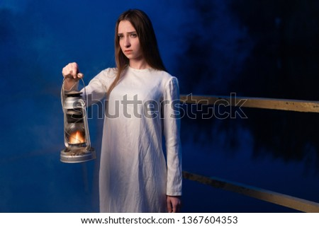 Mysterious mystical girl in a dark night forest with a kerosene lamp in her hands Halloween concept #1367604353