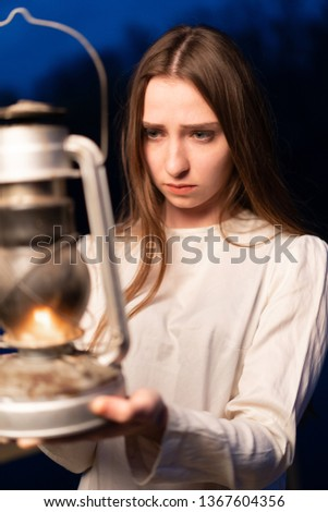 Mysterious mystical girl in a dark night forest with a kerosene lamp in her hands Halloween concept #1367604356