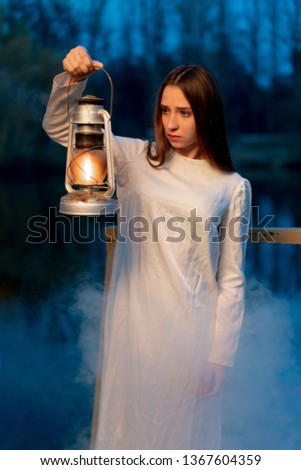 Mysterious mystical girl in a dark night forest with a kerosene lamp in her hands Halloween concept #1367604359