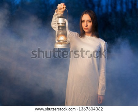 Mysterious mystical girl in a dark night forest with a kerosene lamp in her hands Halloween concept #1367604362