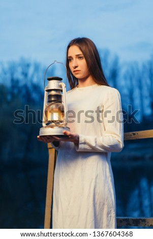 Mysterious mystical girl in a dark night forest with a kerosene lamp in her hands Halloween concept #1367604368