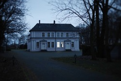 Mysterious, old, haunted mansion house in spooky late autumn scenery