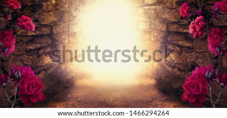 Mysterious photo background with magical trail leading out through stone dungeon cave towards mystical glow and fantastic burgundy colored rose flowers. Idyllic tranquil fantasy scene with empty space