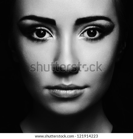Mysterious portrait of a beautiful young woman. Black and white photo