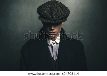 Mysterious portrait of retro 1920s english gangster with flat cap.