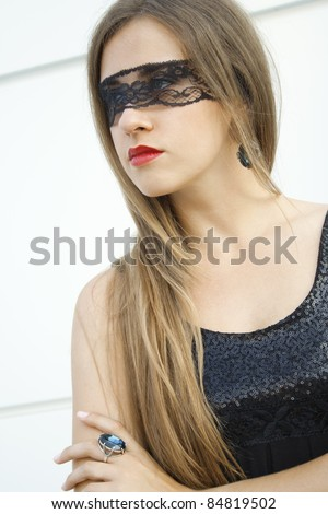 Mysterious pretty fashionable girl blindfolded black lace ribbon on a finger ring fit with a large blue gemstone - stock photo