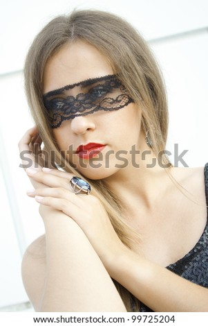 Mysterious pretty fashionable girl blindfolded black lace ribbon on a finger ring fit with a large blue gemstone