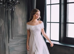 mysterious pretty lady with blond curly hair looks down modestly, enchanted girl in chic light white long vintage dress with open shoulders in dark cloak, princess in gothic castle with large windows.