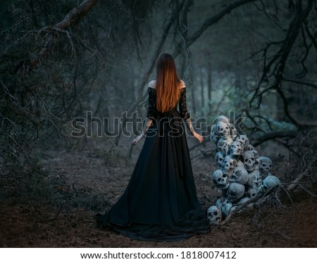 Mysterious silhouette of a ghost woman in a black vintage long dress. Gothic pagan lady near many skulls of dead people. The vampire walks in a deep dark mystical forest. Back rear view.