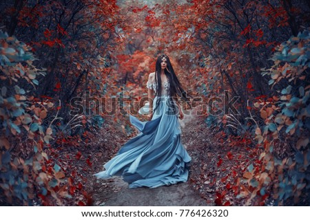 Mysterious sorceress in a beautiful blue dress. Her hair and dress are fluttering in the wind. Background bright, autumn, fiery forest trees with cold tones. Gothic Art Photography. Young nymph