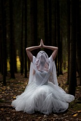 Mysterious woman bride in a gloomy forest in a prayer pose.