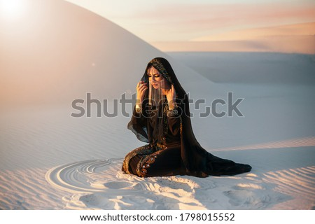 mysterious woman in abaya black long dress sits in desert nature. Luxury clothes, gold accessories hide face. Oriental beauty fashion model. Sand dunes background, orange sunset Art photo pretty lady