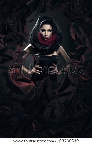 mysterious woman in black hood in dark fabric