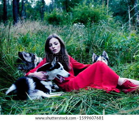 Mysterious woman in red dress with tree wolfs, forest, husky dogs mystery portrait