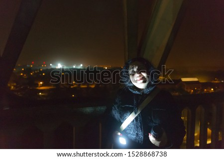 Mysterious woman in the dark with partial illumination of her smiling face on a mystery night in a tower with few lights in the background