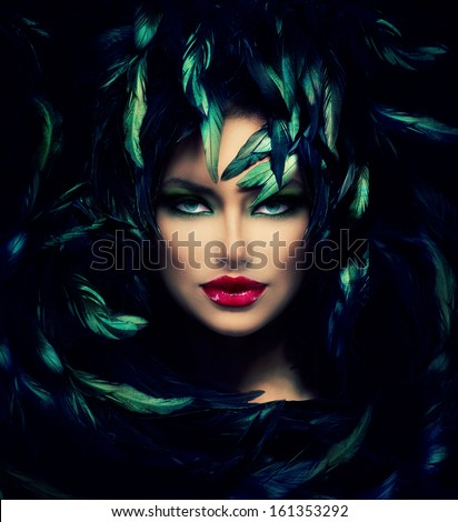 Stock Photo Mysterious Woman Portrait. Beautiful Model Woman Face Closeup. Feathers Hairstyle. Darkness.