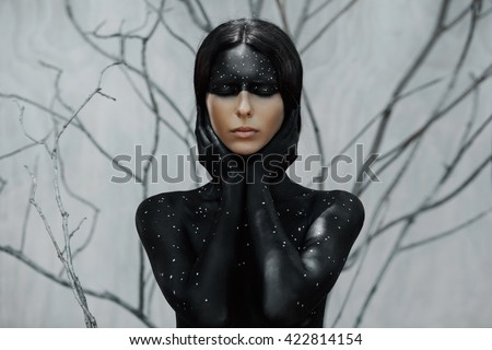 Stock Photo Mysterious woman portrait with branches background. Body art with moon and stars.