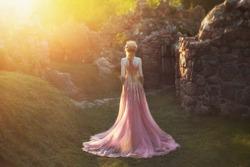 mysterious woman silhouette without face back. Fantasy princess  blond hair gold crown. light pink dress ornaments long train vintage royal clothes. Queen walks garden medieval castle magic sun divine