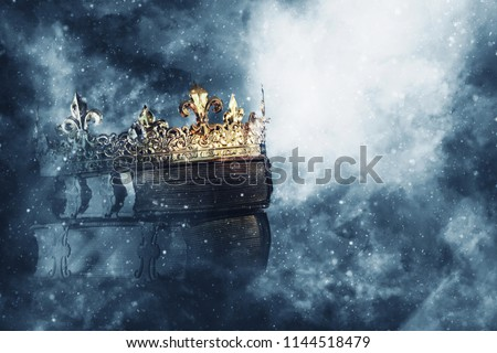 mysteriousand magical image of old crown and book over gothic black background. Medieval period concept