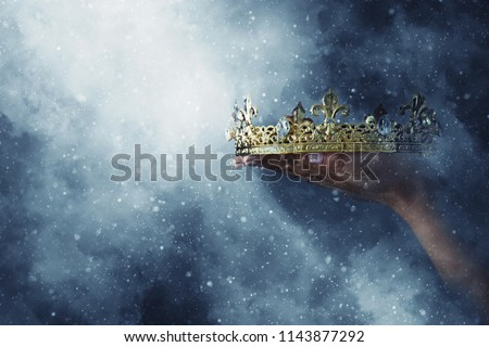mysteriousand magical image of woman's hand holding a gold crown over gothic black background. Medieval period concept