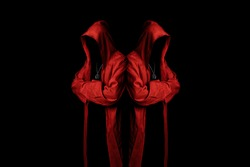 Mystery cult members in a red hooded cloaks in the dark. Unrecognizable person. Hiding face in shadow. Ghostly figure. Sectarian. Conspiracy concept.