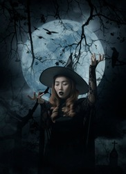 Mystery halloween witch standing over cross, church, crow, birds, dead tree, full moon and cloudy spooky sky, Halloween mystery concept