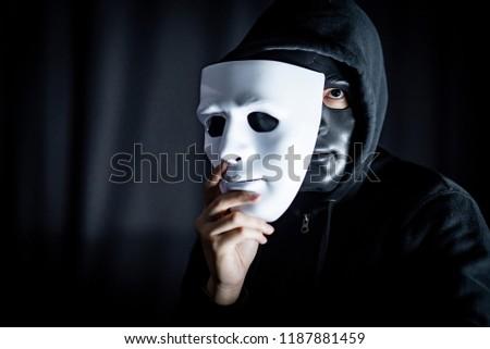 Mystery hoody man wearing black mask holding white mask. Anonymous social masking. Major depressive disorder or bipolar disorder. Halloween concept
