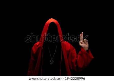Mystery man in a red hooded cloak in the dark. Unrecognizable person. Hiding face in shadow. Pointing up with fingers. Ghostly figure. Sectarian. Conspiracy concept.   Stock photo ©