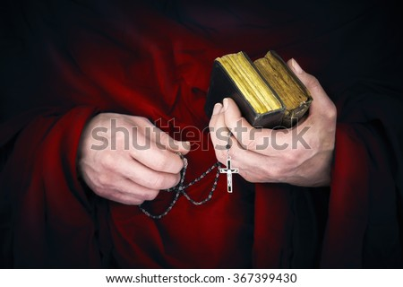 Mystery monk with a cape holding bibles and a black rosary in his hands