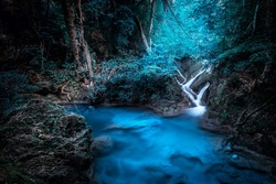 Mystery night at deep tropical rain forest with flowing cascade waterfall. Fantasy jungle landscape.  Erawan, National Park Kanchanaburi, Thailand