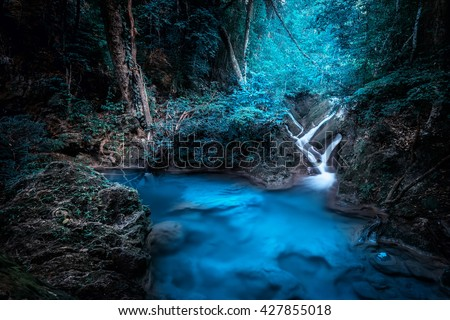 Mystery night at deep tropical rain forest with flowing cascade waterfall. Fantasy jungle landscape.  Erawan, National Park Kanchanaburi, Thailand stock photo