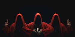 Mystery people in a red hooded cloaks in the dark. Hiding face in shadow. Pointing up with fingers. Satanic symbols. Ghostly figure.