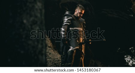 Mystery scarface knight in armor with sword and crossbow in the forest